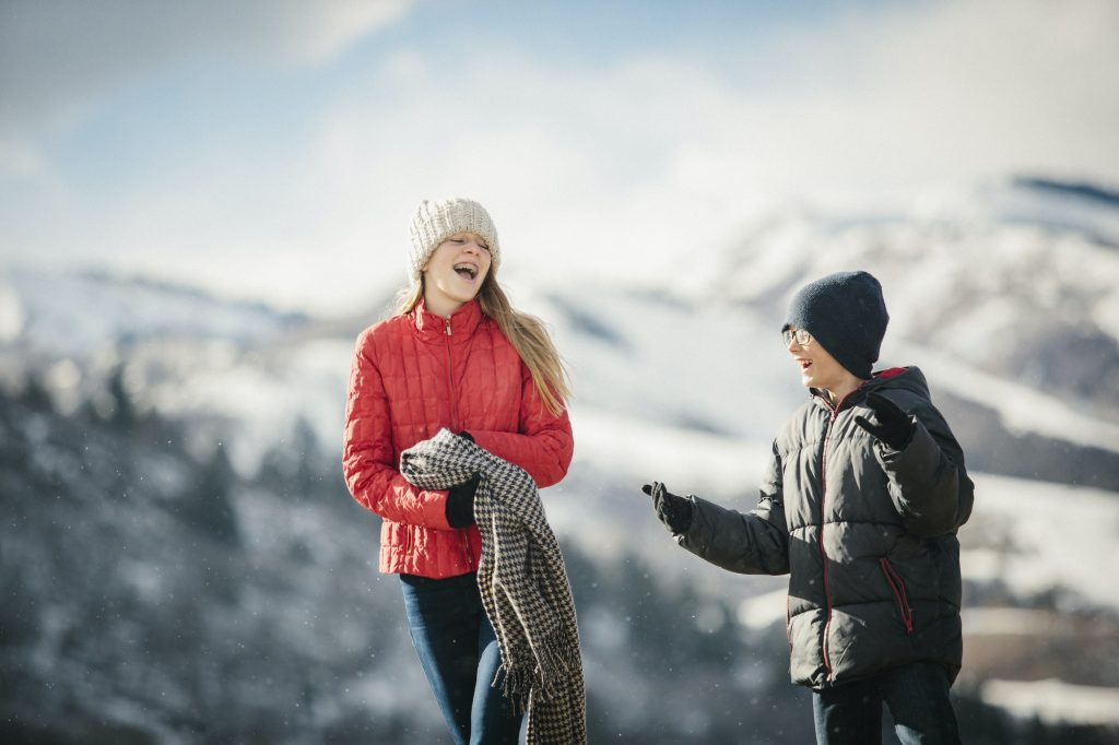 A brother and sister together outdoors in the winter, laughing.